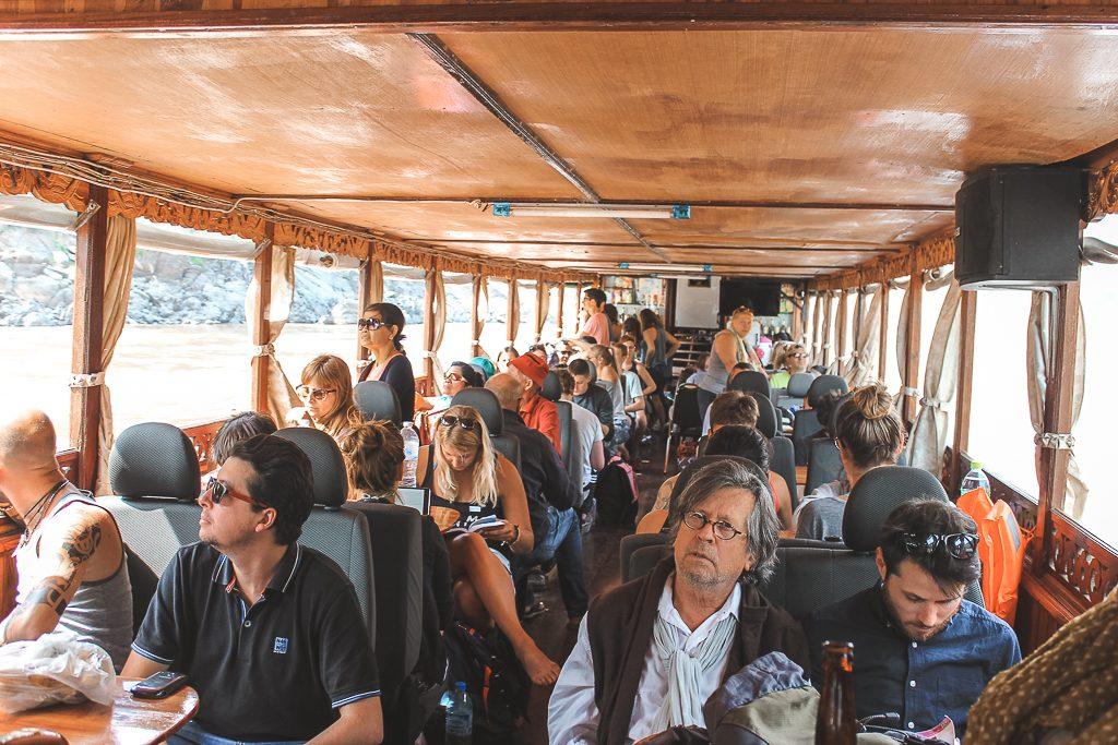 Mensen op autostoelen in houten boot op slowboat naar Luang Prabang.