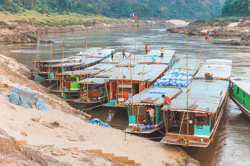 Steile zandberg met vijf keer een houten slowboat naar Luang Prabang