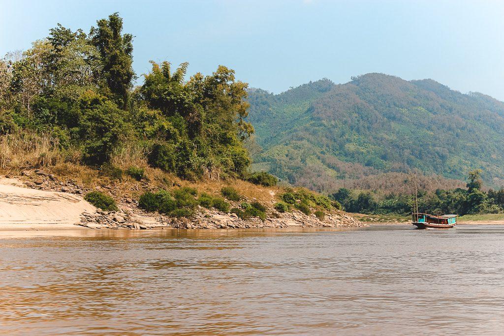 De bruine Mekong-rivier met aqua gekleurd houten bootje op achtergrond.