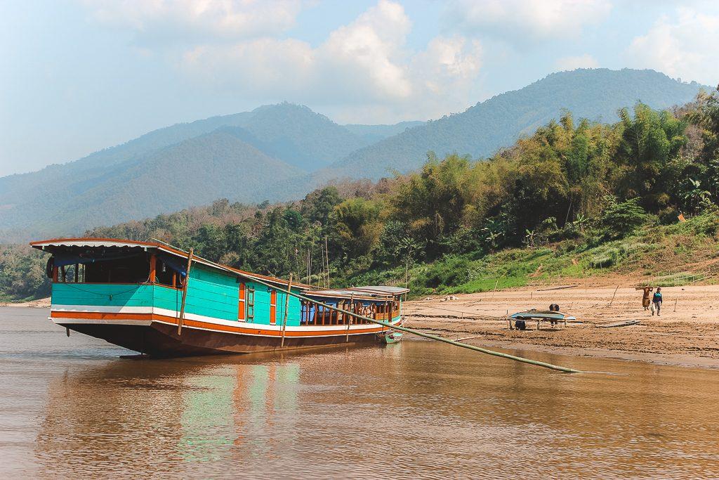 Een aqua gekleurde houten boot op een zandoever bij donkerbruine Mekong-rivier.