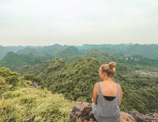Vrouw die uitkijkt over heuvels met begroeiing in Vietnam.