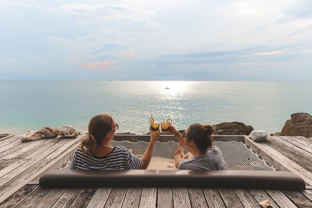 eerste keer alleen reizen: twee mensen proosten op terras aan zee.