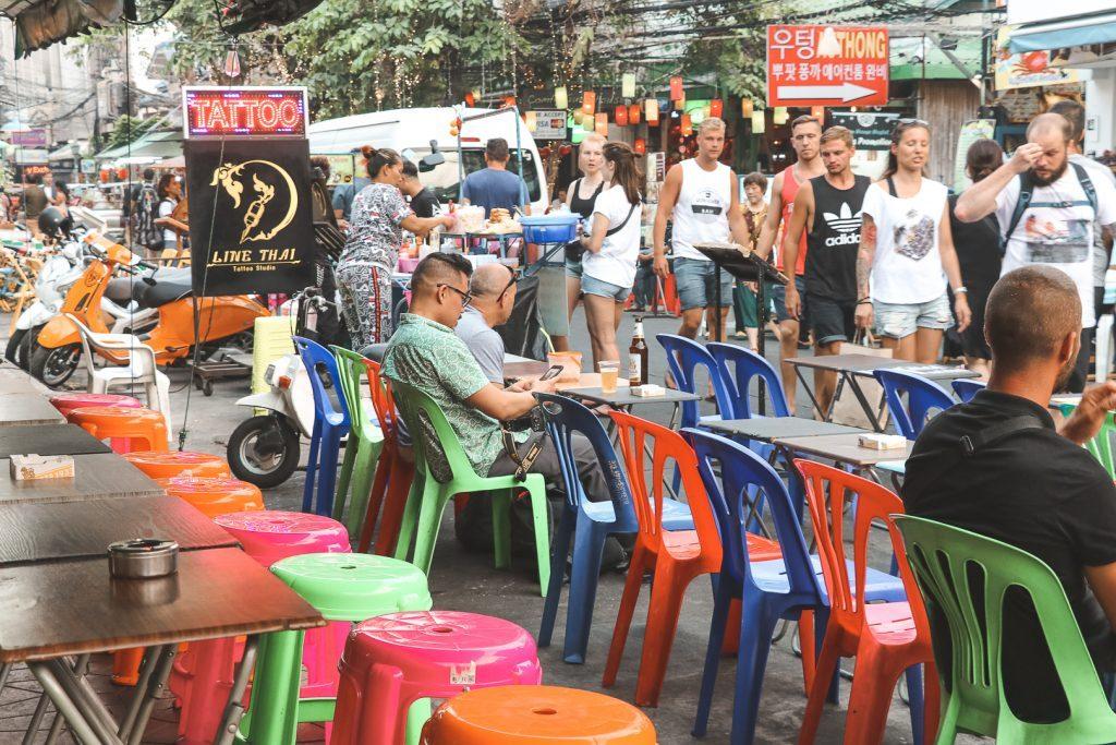 Gekleurde plastic stoeltjes en voorbijgangers op Khao San Road.