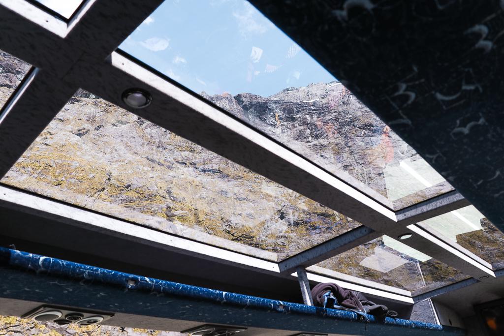 De bus met glazen dak van JUCY naar Milford Sound