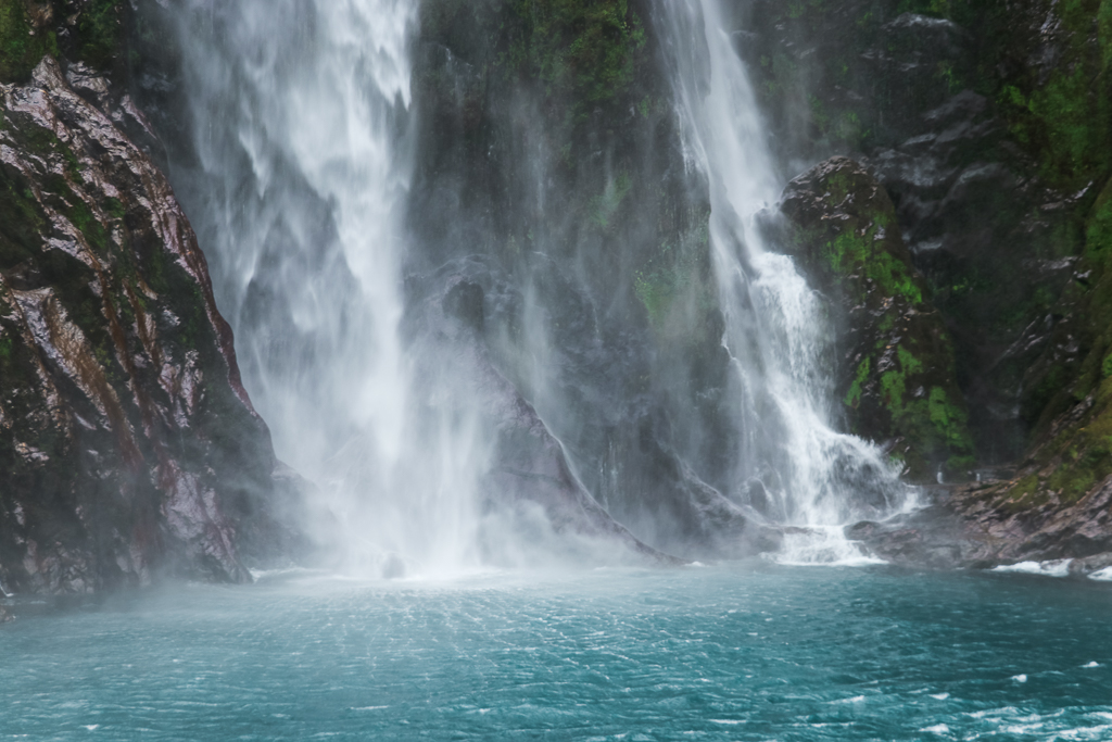 De catamaran vaart dicht naar de waterval toe in Milford Sound.