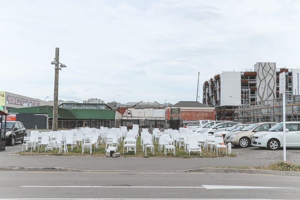 185 witte stoelen als memorial op grasveld bij weg.