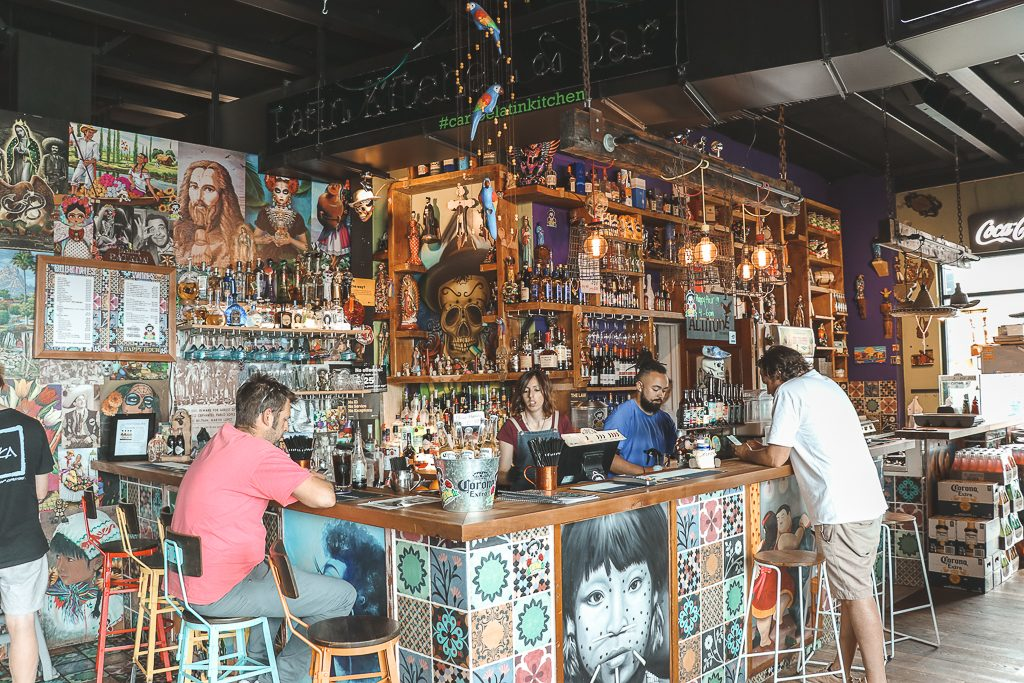 Bar in Mexicaanse sfeer met veel flessen en kleur bij Little High Eatery