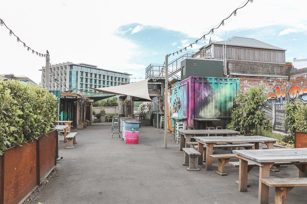 Geverfde containers, houten bankjes en lampjes op het betonnen terras van Smash Palace in Christchurch