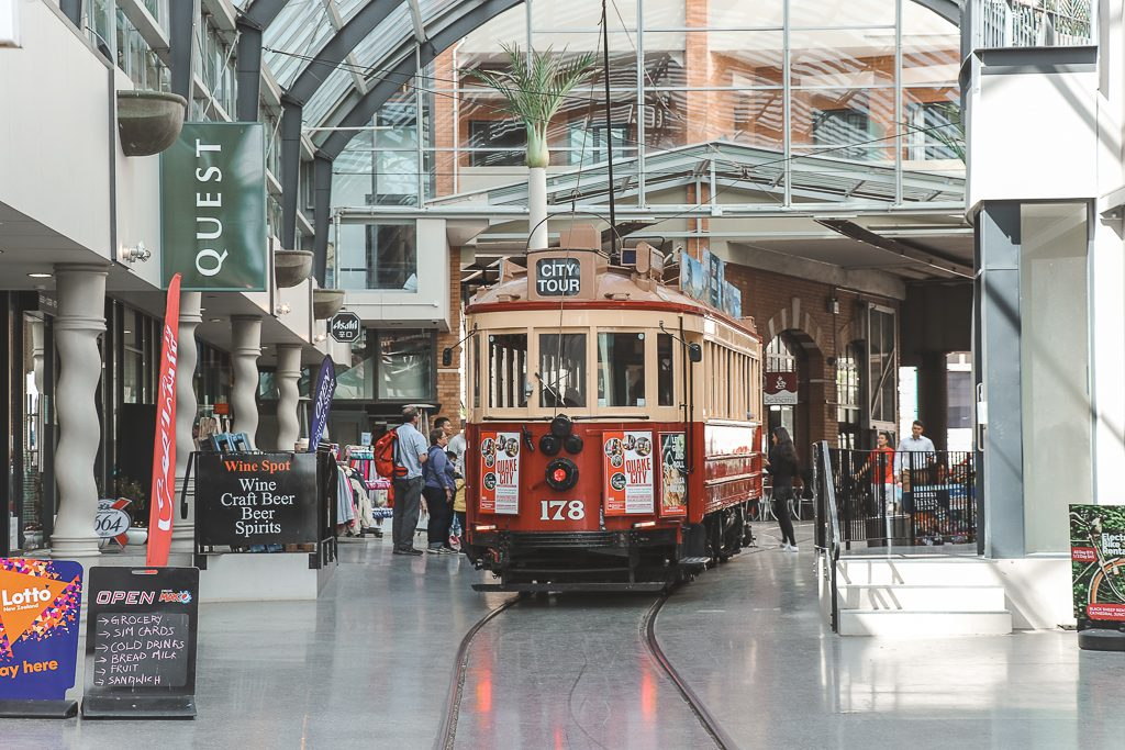 Een rood-crèmekleurige historische tram in een met glas overdekt winkelcentrum in Christchurch.