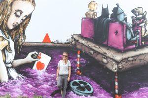 Persoon voor muur met paarse illustratie in Christchurch.