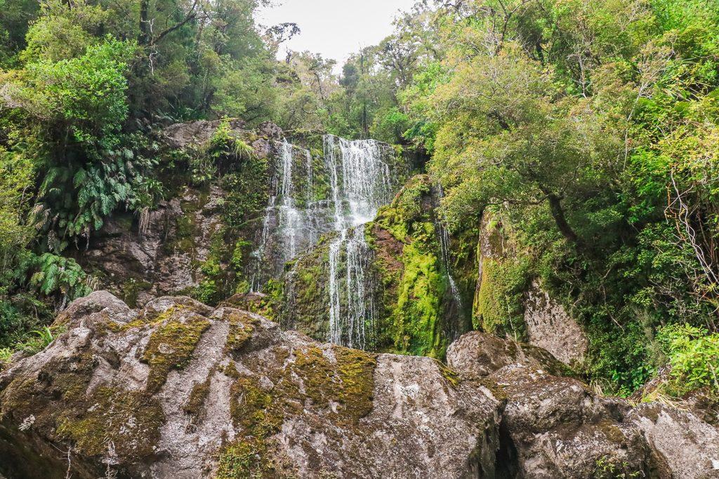 Waterval bij rotsen en bomen - Rondreis Zuidereiland