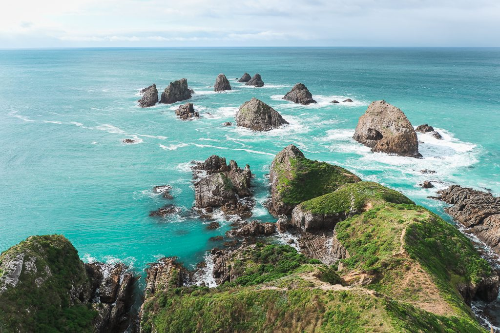 Hoogtepunten Zuidereiland: Rotsen in felblauwe zee en groene kustlijn