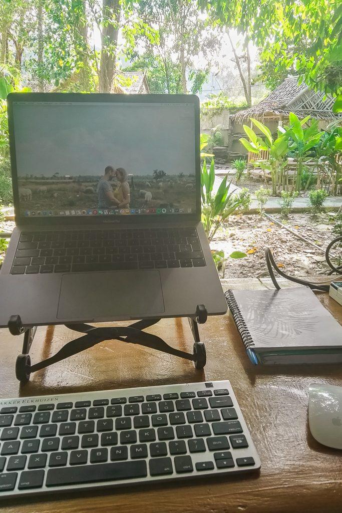 Laptop op standaard in tropische tuin.