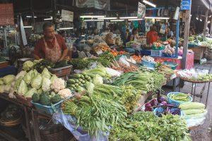 Groene groenten op een markt met koopman.