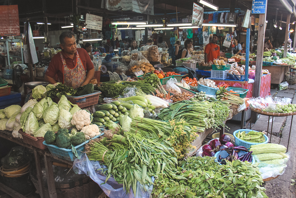 Groene groenten op een markt met koopman om Thaise kip met cashewnoten mee te maken.