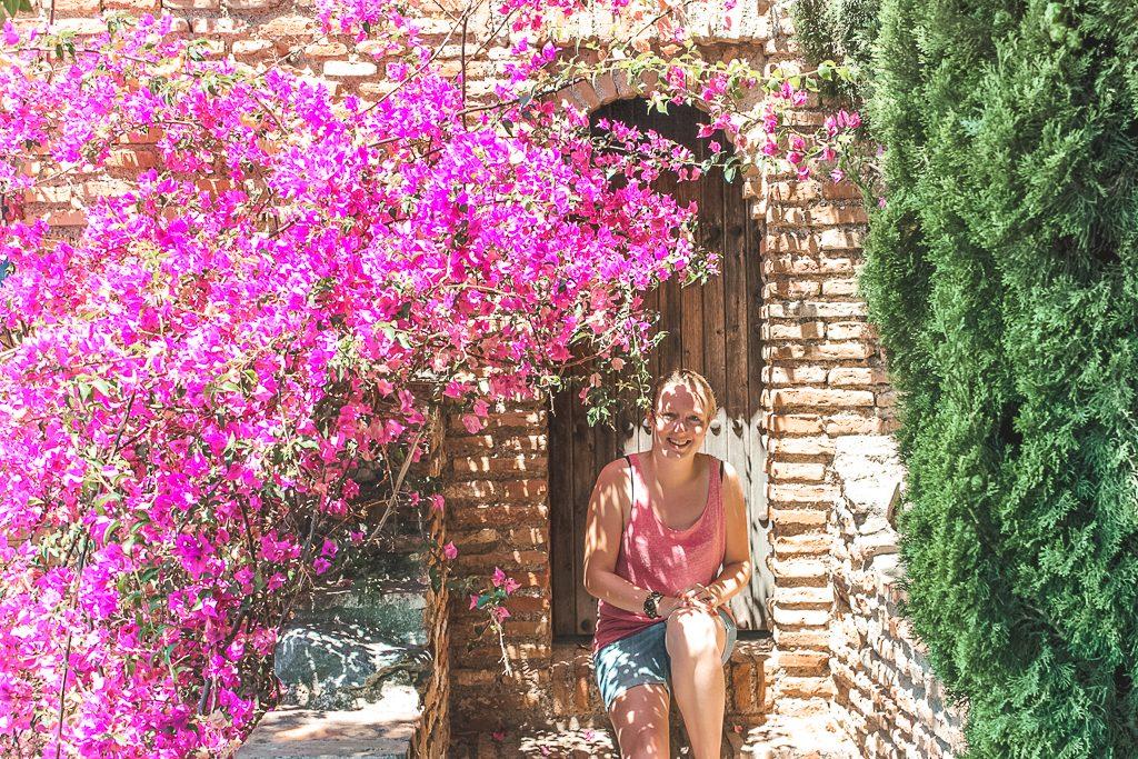 Vrouw zitten bij houten deur in stenen muur naast roze bloemen.