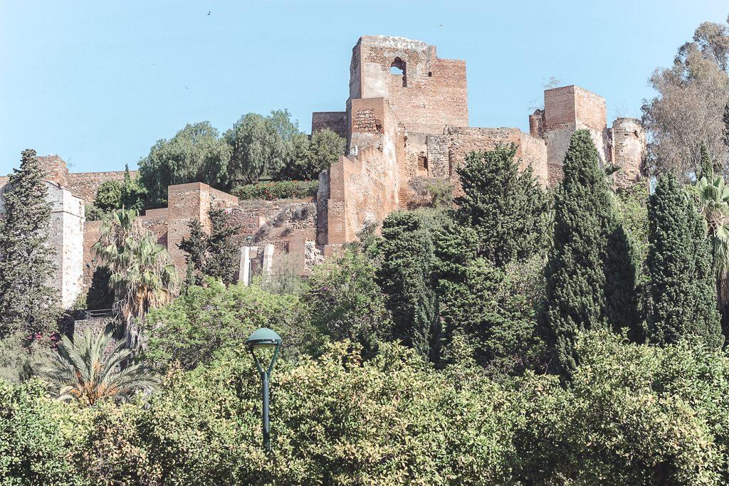 Ruïnes van kasteel Gibralfaro tussen groene bomen tegen blauw lucht.