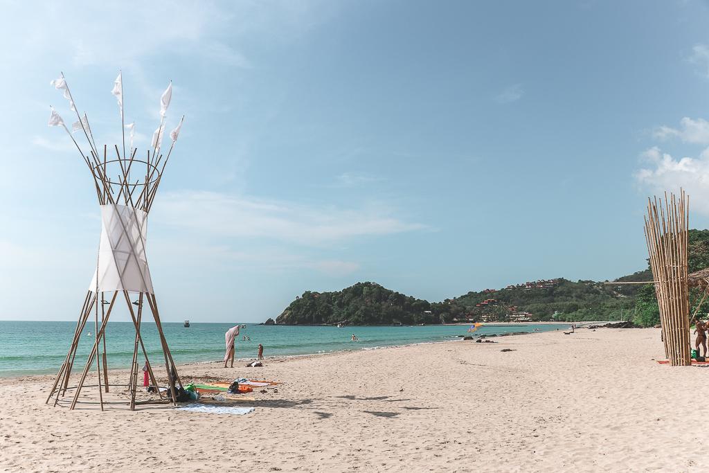 Strand met blauw water, jungle en bamboostokken als tipi op Koh Lanta.