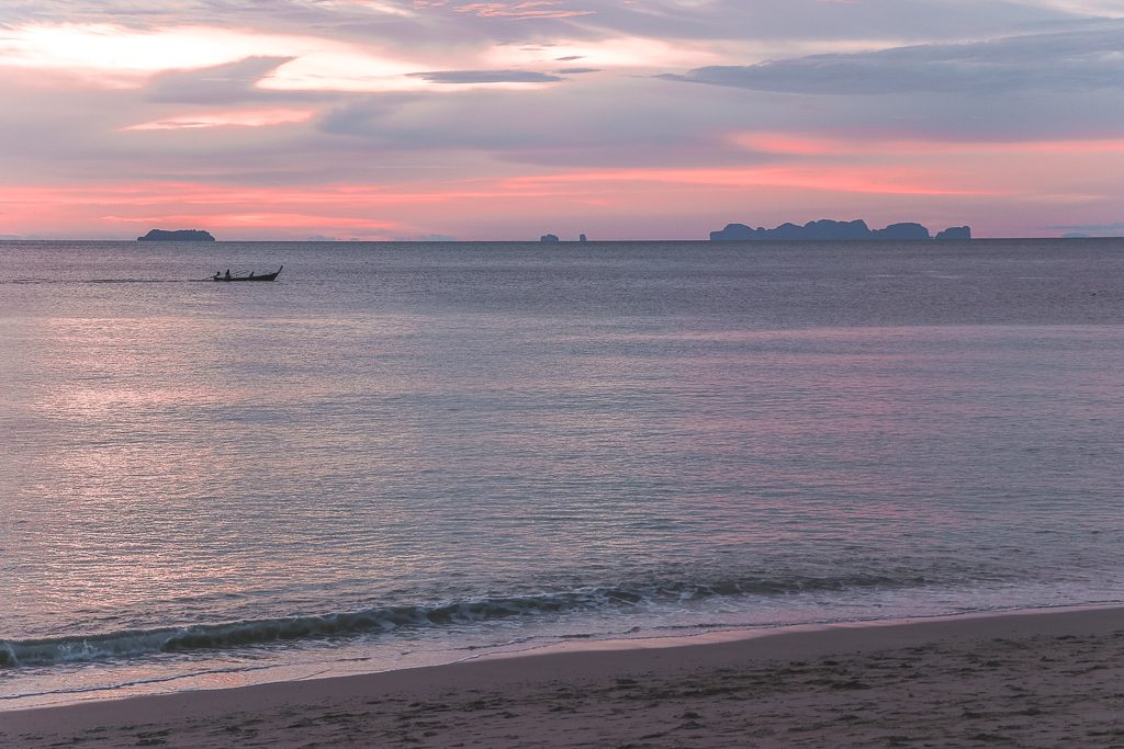 Boot op zee tegenover roze zonsondergang op Koh Lanta.