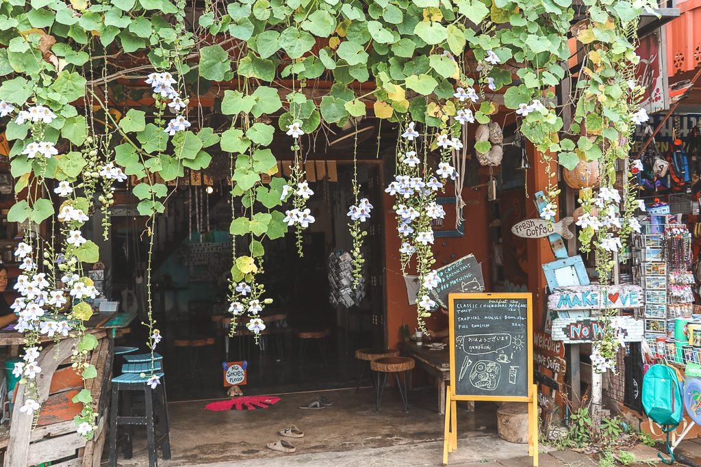 Houten café met hangende bladeren en bloemen voor ingang.