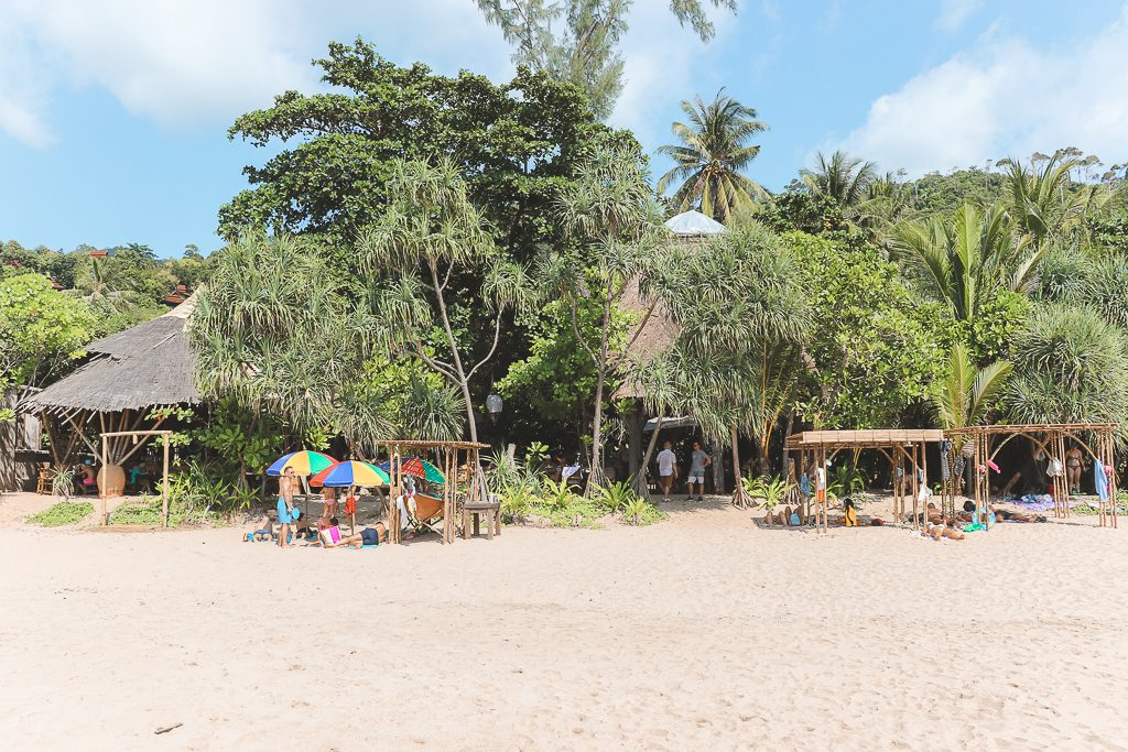 Groene bomen en bamboe restaurant op wit strand.