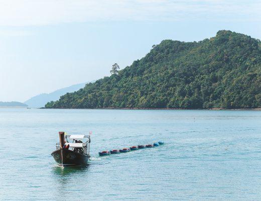 Longtail boot met rij kano's en eiland bij Koh Lanta Ngoi.