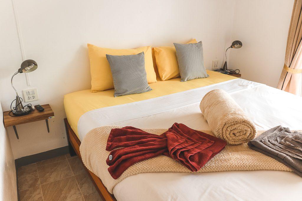 Bed met gele en grijze kussenhoezen en wit dekbed Kohub appartement.
