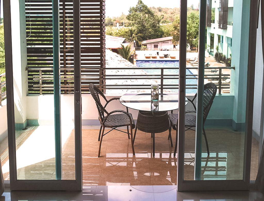 Uitzicht over balkonnetje met stoelen en zwembad op achtergrond.