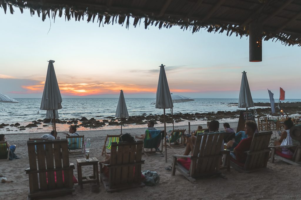 Strandstoelen en parasols op strand bij zonsondergang Koh Lanta.
