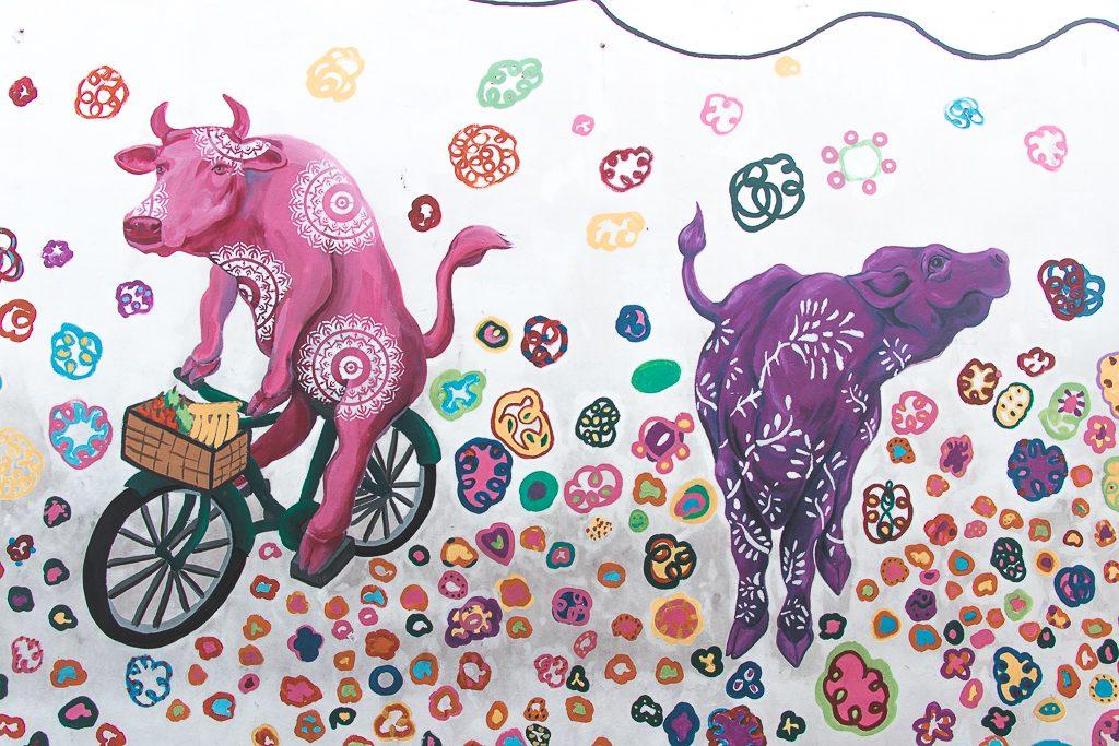 Tekening van roze en paarse koe op muur