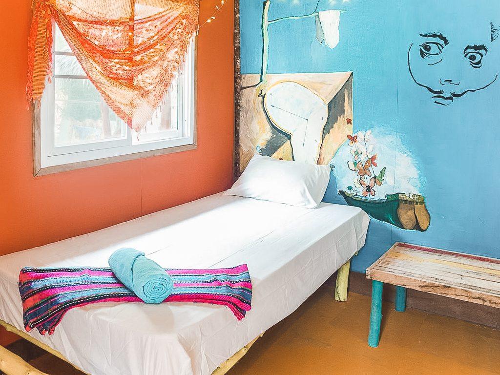Wit eenpersoons bed in kamer met blauwe muur en oranje muur