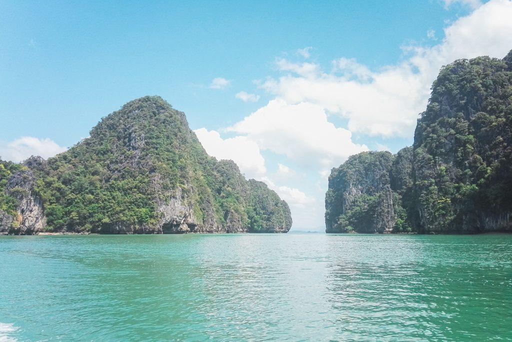 Krijtstenen begroeide rotsen die uit azuurblauw water steken bij Koh Phee.
