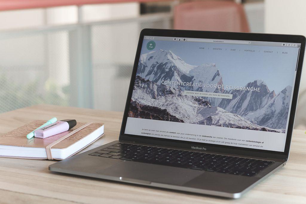 Laptop met agenda en twee pennen op houten tafel.