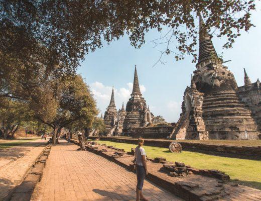 Vrouw die kijkt naar drie stenen stoepa's op grasveld bij Wat Phra Si Sanphet.