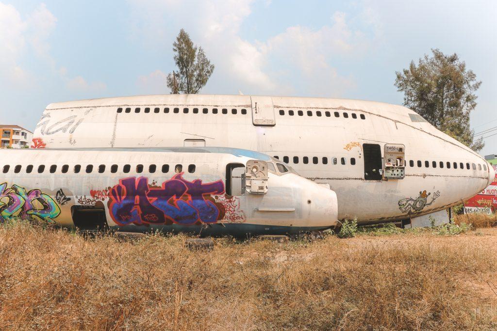 Twee lege vliegtuigen met graffiti en dor weiland.