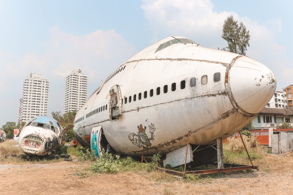 Lege Boeing naast klein vliegtuig op veld in Bangkok.