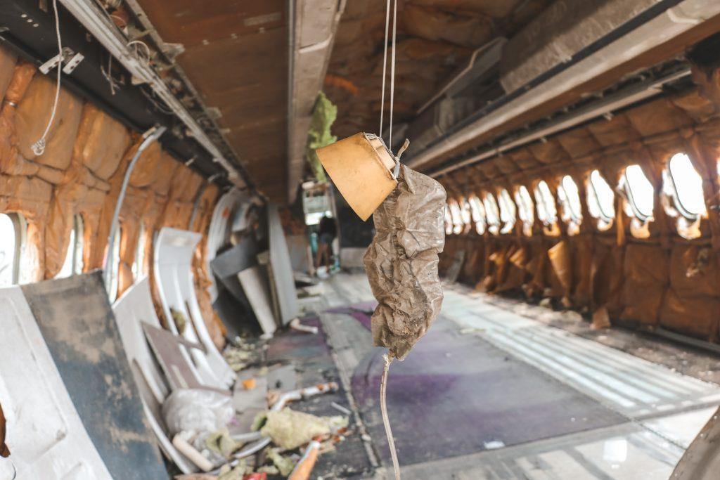 Zuurstofmasker dat hangt in gestript vliegtuig.