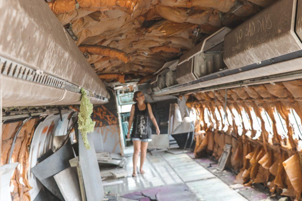 Meisje dat loopt in een leeg, gestript vliegtuig op Airplane Graveyard.
