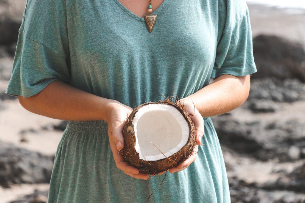 Kokosnoot in handen van vrouw met blauwe jurk.