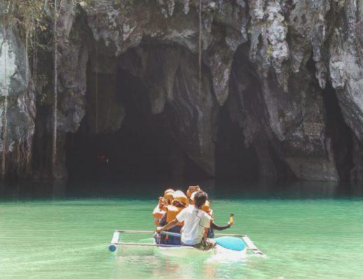 Een boot met mensen dat vaart richting een underground river op Palawan.