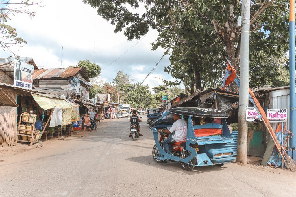 Stoffige straat met blauwe tricycle in Puerto Princesa.
