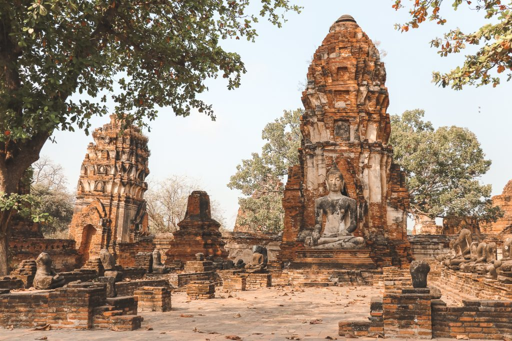 Historische tempel met boeddha bij boom in Wat Phra Mahathat.