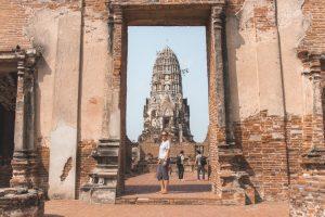 Cilindervorminge tempel gezien vanuit stenen poort bij Wat Ratburana in Ayutthaya.