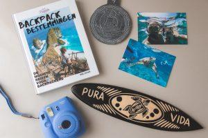 Flatlay van het boek Backpack bestemmingen, polaroid, souvenirs en foto's.