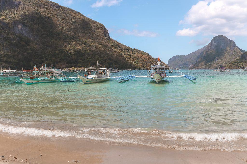 Azuurblauw water met gekleurde vissersboten en rotsige eilanden bij El Nido.