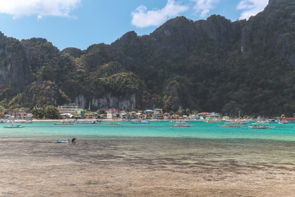 Azuurblauw water met op achtergrond het stadje El Nido op Palawan.