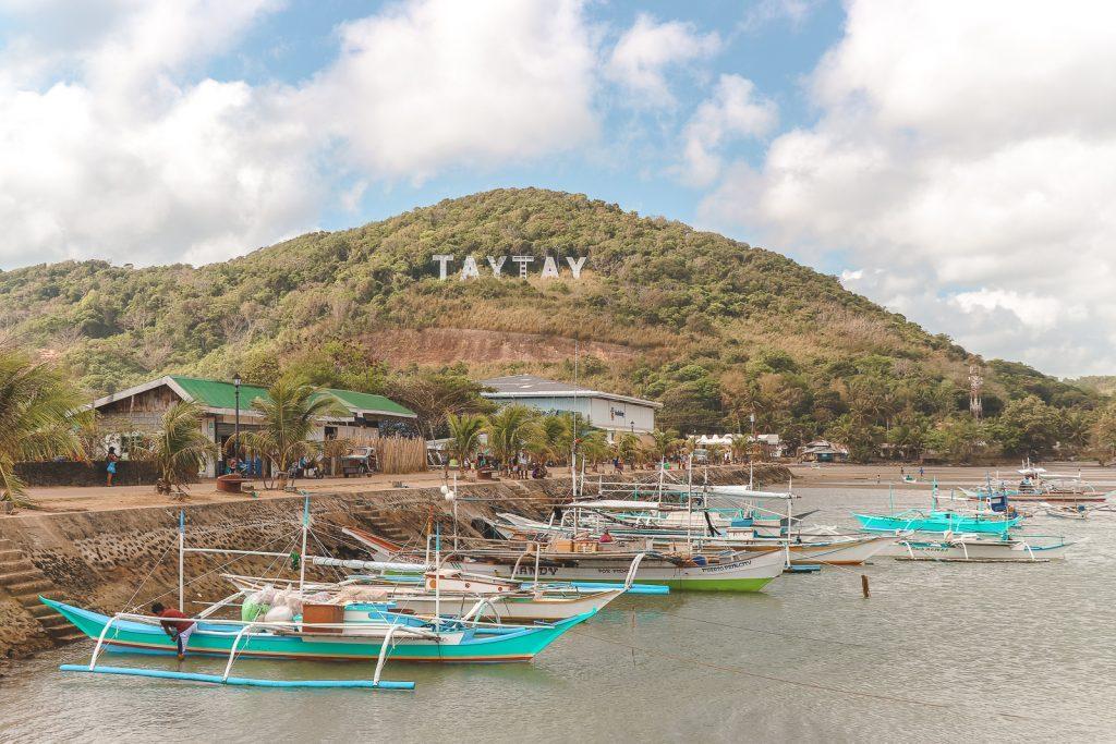 Hollywoodletters op heuvel en blauwe vissersboten in zee bij Taytay.