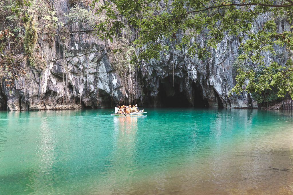 Longtailboot met toeristen die naar grot varen.