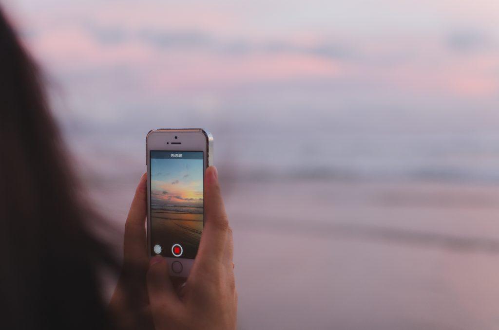 Foto op telefoon van roze zonsondergang