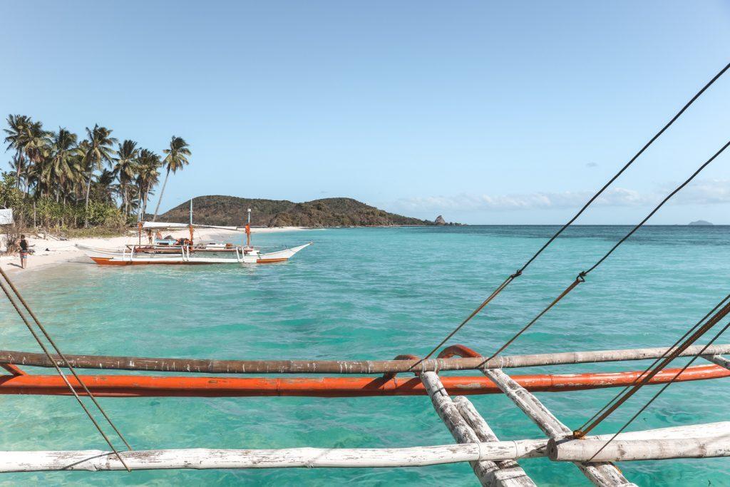 Uitzicht vanaf houten reling op azuurblauw water Filipijnen.